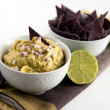 Guacamole with Red Onion and Blue Corn Chips — Stock Photo