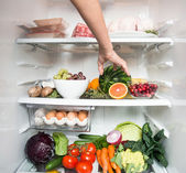 Hand Reaching for Snack in Refrigerator Full of Healthy Food Options — Stock Photo