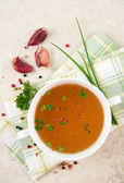 Bone Broth in Small Soup Bowl Served with Fresh Herbs, Garlic and Spices — Stock Photo