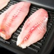 Stock Photo: Closeup of Raw Rock Fish Grilled on Griddle with Some Herbs and Spices