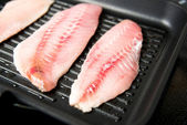 Closeup of Raw Rock Fish Grilled on Griddle with Some Herbs and Spices — Stock Photo
