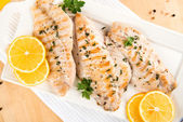 Closeup of Dinner Plate with Grilled White Fish and Lemons — Stock Photo