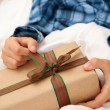 Child's Hands Opening Present in Bed — Stock Photo