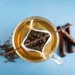 Clear Glass Cup of Loose Green Tea in Paper Filter Bag with Some Chocolate Sticks — Stock Photo #29075235