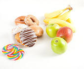 Pile of Unhealthy Tempting Food and Healthy Fruits — Stock Photo