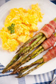 Asparagus Wrapped in Bacon and Served with Scrambled Eggs — Stock Photo