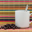 Cup, candies and spoon on a color background — Stock Photo