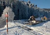 Snowy railroad crossing under the rocks — Stock Photo