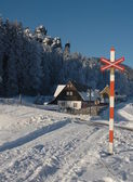 Snowy railroad crossing beneath the Adršpach rocks with a house — Foto Stock