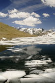 Mountain lake with ice floes in mountains — Stock Photo