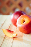 Peaches with a slice of a peach on a wooden table — Foto Stock