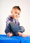 Retrato de menino adorável bebê sentado com as mãos sob o queixo — Fotografia Stock