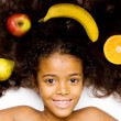Beautiful mixed race girl with fruits — Stock Photo