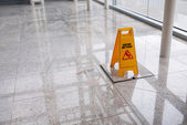 Wet floor sign on lobby floor — Stock Photo
