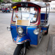 Stock Photo: Tuktuk on street with temple background in Bangkok