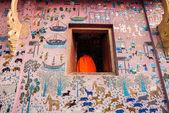 Luang Prabang, LAOS - FEB 10: A novice monk through a temple win — Stock fotografie