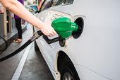 Female hand holding green pump filling gasoline — Stockfoto