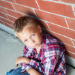 Stock Photo: Young Boy Sitting Against Wall