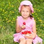Cute girl eating strawberries — Stock Photo