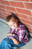Young Boy Sitting Against a Wall — Stock Photo