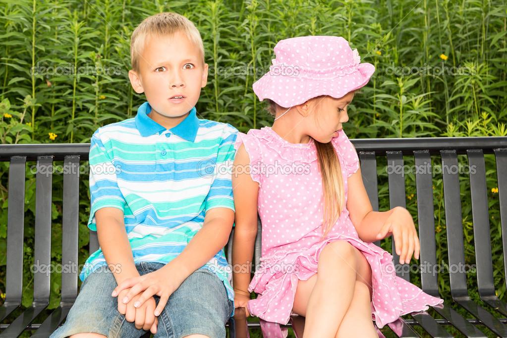两个可爱的孩子坐在公园长凳上