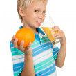 School-Aged Boy Holds a Glass with an Orange Juice with One Hand — Stock Photo