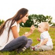 Young beautiful mother feeding her baby puree outdoors in sunlight — Stock Photo #28929147