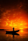 Silhouette of a couple kissing in boat on river in sunset — Stock Photo
