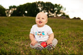 Baby with apple outdoors — Stockfoto