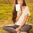 Woman holding blank board outdoors — Stock Photo