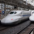 Stock Photo: Two Shinkansen trains depart from rail station.