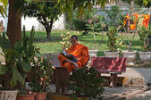 Young laotian monk reads buddhist book in the garden of Wat Ong Teu monastery in Vientiane, Laos — Stock Photo