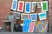 Moroccan artisan sells colorful paintings in the market of Jemaa el-Fnaa in Marrakech medina on May 21, 2012. — Stock fotografie