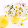 Still life with apple and a cup with white chrysanthemums — Stock Photo