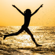 The silhouette of a girl, running along the seashore — Stock Photo