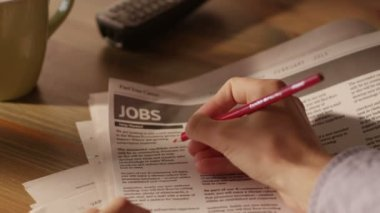 Man Looking for Job in a Newspaper and Marking Advertisement Using Red Pencil — Stock Video