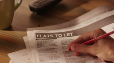Man Marking Advertisement of Flats in a Newspaper Using Red Pencil. — Stock Video