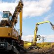 Stock Photo: Two excavators working on scrapyard.