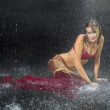 Beautiful woman in red lingerie lying under the rain — Stock Photo #31447437