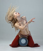 Beautiful expressive blond girl in east suit playing on a drum — Stock fotografie