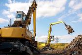 Two excavators working on the scrapyard. — Stock Photo