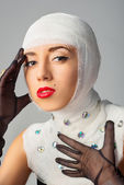 Beautiful woman with bandages on her head — Stockfoto