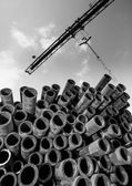 Crane and stack of pipes — Стоковое фото
