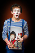 Clown grimacing with poster of two clowns — Stock Photo