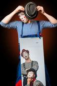 Palhaço fazendo careta com poster de dois palhaços — Fotografia Stock