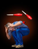 Clown playing with bowling pins — Stock Photo