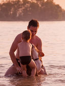 Father and son full around with beagle dog in the river water — Stock Photo