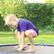 Cheerful blond boy jumping on trampoline in the summer garden — Видео