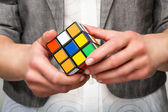 Hands holding or playing color cube — Stock Photo