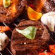 Beef steak on a barbecue grill with flames with vegetables — Stock Photo #46393731